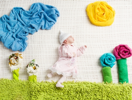 Newborn baby lying on creative nature background folded from towels and clothing photo