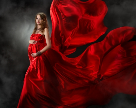 Pregnant woman in red evening dress, wings flying on wind photo