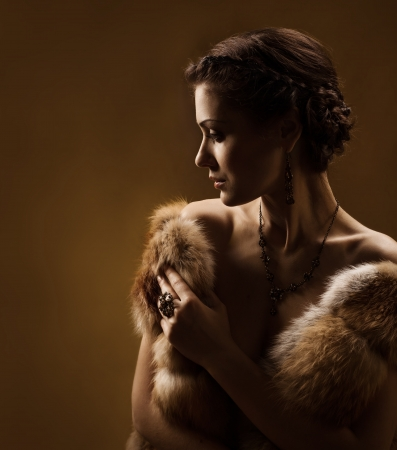 Woman in luxury fur coat  Vintage style  Brown background  photo