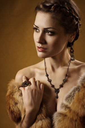 Woman in luxury fur coat  Vintage style  Brown background  Stock Photo - 17515630