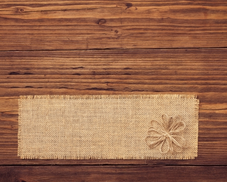 Sackcloth tag over brown wooden board background photo