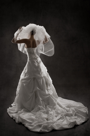 Bride in wedding luxury dress, back view, raised hands up. Black background