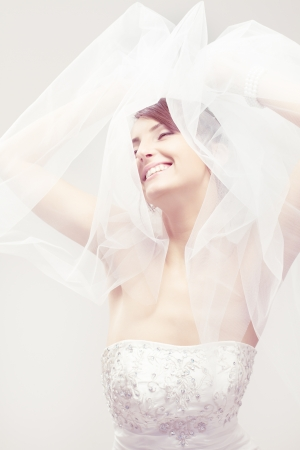Happy bride smiling, closed eyes, carefree dreaming. Over white photo