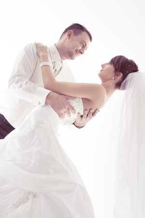 Wedding couple happy smiling and dancing. Groom and bride portrait. Over white photo
