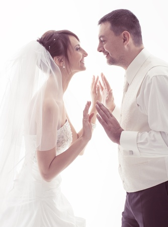 Bride and groom face-to-face holding hands over white background photo
