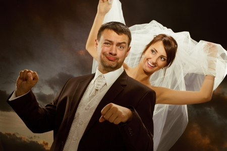 bride and groom background: Wedding couple have fun. Smiling bride and groom imagine driving by bike Stock Photo