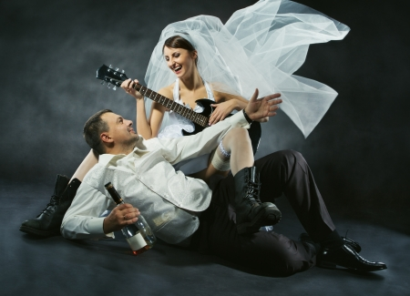 wedding party: Wedding couple celebrating, singing, drinking and playing guitar. Bride in rock style.  Stock Photo