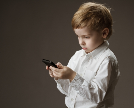 Boy playing game on cell phone. Kid holding mobile on grey background photo