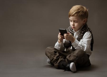 ni�os pensando: Ni�o que juega al juego en el tel�fono celular. Kid sentado sobre fondo gris y la celebraci�n de m�vil Foto de archivo