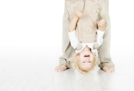 Child standing head over heels. Funny up portrait. Parent legs. Stock Photo - 17953684