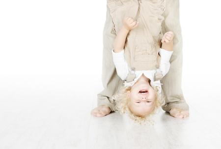 Child standing head over heels. Funny up portrait. Parent legs. Stock Photo - 17953684