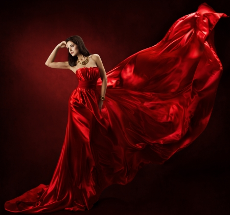 Woman in red waving Kleid tanzt mit fliegenden Stoff photo