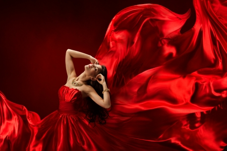 wind dress: Woman in red dress blowing with beautiful flying fabric Stock Photo