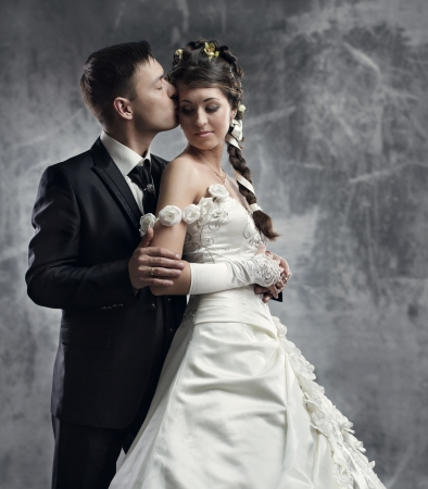 tender's: Bride and groom at gray grunge background. Wedding couple fashion shoot.