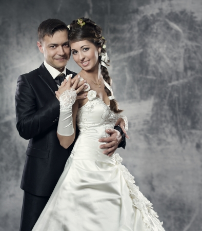 wedding portrait: Bride and groom at gray grunge background. Wedding couple fashion shoot.