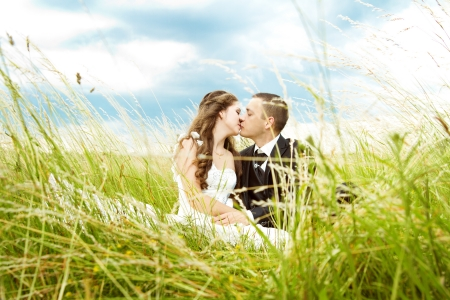 Beautiful bride and groom  kissing in grass.  Wedding couple outdoors   photo