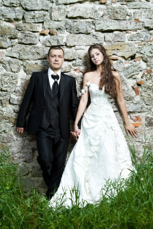 Bride and groom over stone brick wall outdoors photo
