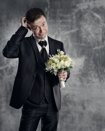 Thoughtful groom with flowers bouquet. Gray background. Stock Photo - 18916266