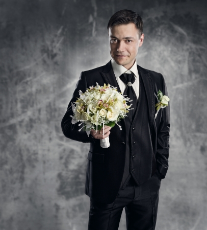 Man in black suit with flowers bouquet. Wedding groom fashion. Gray background. photo