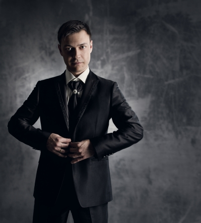 Handsome man in black suit. Wedding groom fashion. Gray background. photo