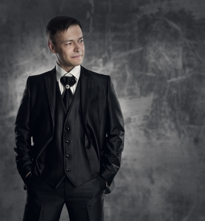 ceremonial clothing: Handsome man in black suit. Wedding groom fashion. Gray background. Stock Photo