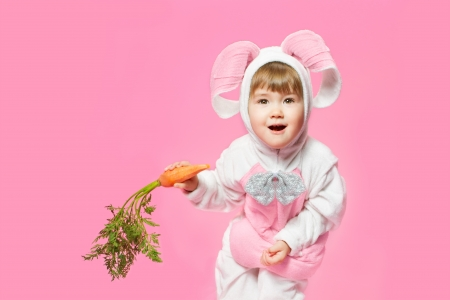 Child in bunny hare costume holding carrots. Pink background photo