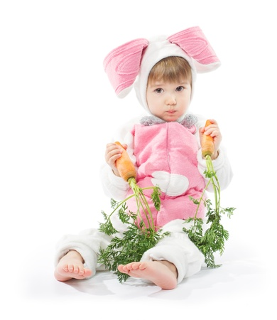 Child in bunny hare costume holding carrots. White background photo