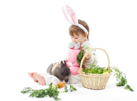 Child in bunny hare costume holding rabbit and carrot. White background photo