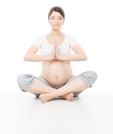 pregnancy yoga: Pregnant woman relax doing yoga, sitting in lotus position over white background
