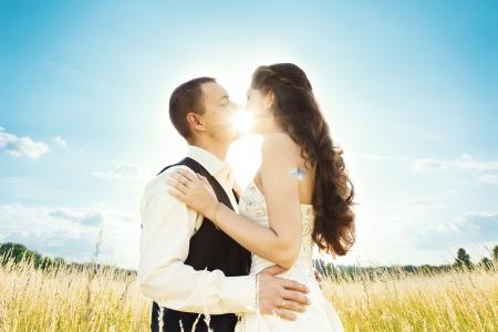 Wedding couple bride and groom in nature. sun shine through kiss photo