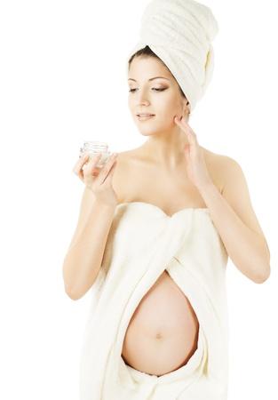 mujeres embarazadas: Mujer embarazada spa, cuidado de la piel de la salud y la belleza del embarazo. Envuelto en toallas de ba�o, aplicaci�n de crema