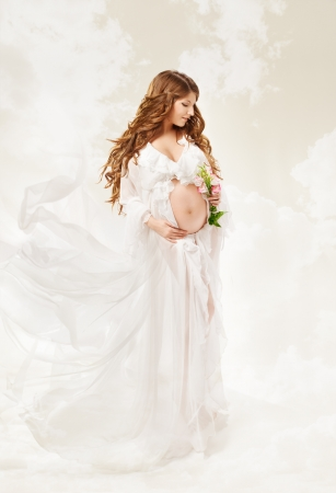 Pregnant woman. Beautiful pregnancy: long curly hair and chiffon dress fluttering on wind. photo