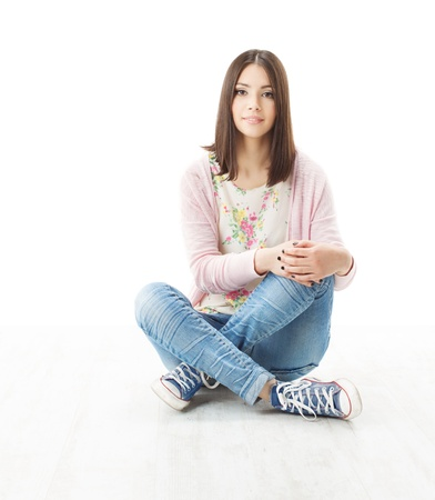 Beautiful girl teenager sitting on floor. White background photo