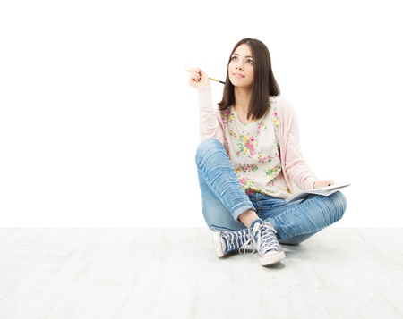 dream planning: Beautiful girl teenager thinking sitting on floor. White background