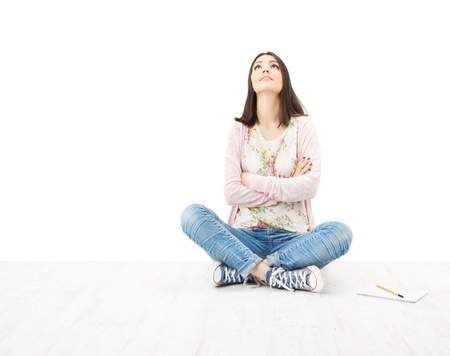Beautiful girl teenager thinking sitting on floor. White background photo