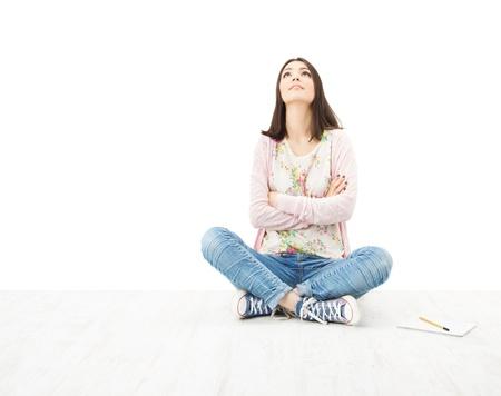 mujer sentada: Hermosa chica pensamiento adolescente sentado en el suelo. Fondo blanco Foto de archivo