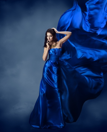 black silk: Woman in blue dress  with flying silk fabric Stock Photo