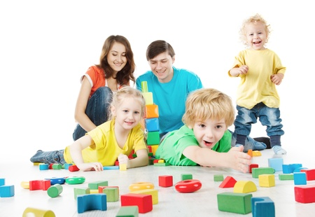 Parents with three kids playing blocks over white photo