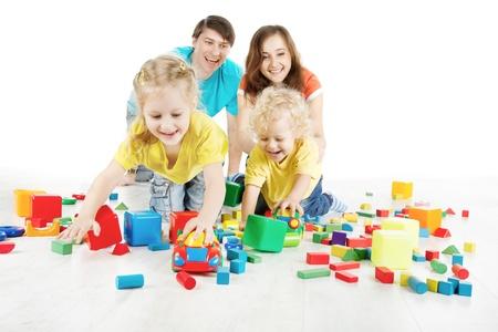 jouet: Les parents avec deux enfants jouant des blocs sur blanc