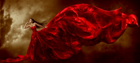 Woman in red waving beautiful dress with flying fabric over artistic sky background photo