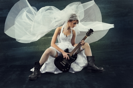 Bride playing rock guitar over artistic dark background photo
