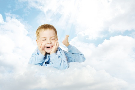 Smiling child lying down on cloud pillow over sky background Stock Photo - 20206357