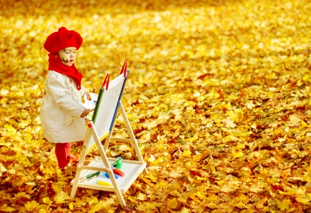 Child drawing on easel in Autumn Park  Creative kids development concept  photo