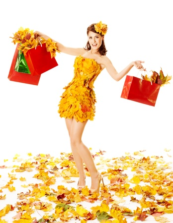 Autumn woman with shopping bags in dress of maple leaves. White background photo