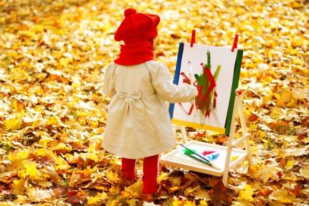 Dibujo niño en la base en el Parque de otoño. Niños creativos concepto de desarrollo. Foto de archivo - 21963469