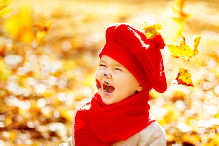 enyoing: Happy smiling child in autumn park enyoing sunshine