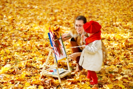 Mother and child drawing on easel in autumn park. Creative kids development concept. photo