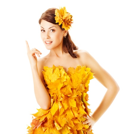 Autumn woman in yellow fashion dress of maple leaves over white background  photo