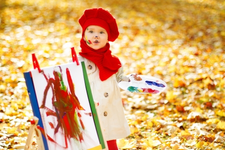 Child drawing on easel in Autumn Park. Creative kids development concept. photo