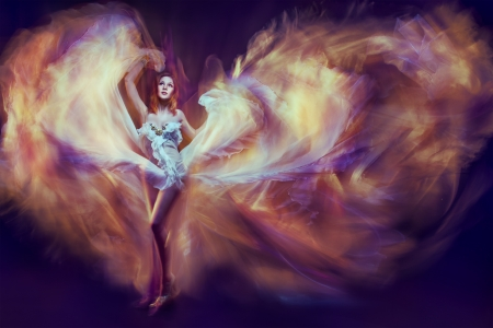 Woman in waving dress as a flame dancing with flying fabric. Dark background photo